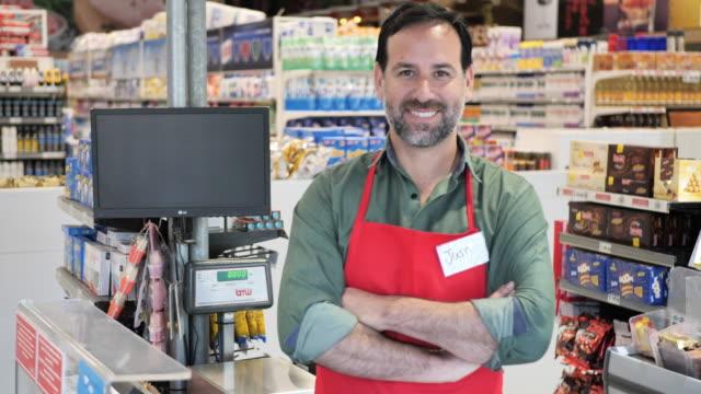 latin american employee , essential worker, cashier in supermarket during pandemic coronavirus - essential workers stock videos & royalty-free footage