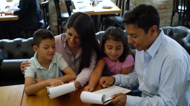 Latin American family at a restaurant looking at the menu deciding what to order Latin American family at a restaurant looking at the menu deciding what to order all smiling menu stock videos & royalty-free footage