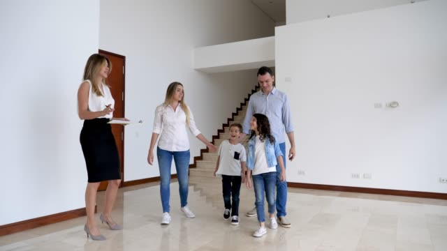 latin american family looking at a property with a real estate agent father pointing at something and kids looking very excited - proprietario d'immobili video stock e b–roll