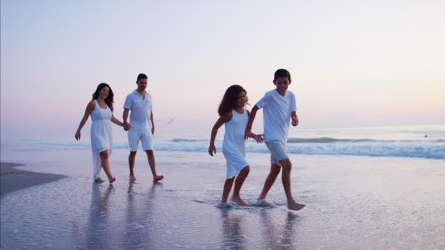 Latin American family walking on beach at sunset