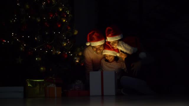 latinamerikansk familj med två barn öppnar julklappar på natten alla mycket glada och glada - christmas gift family bildbanksvideor och videomaterial från bakom kulisserna