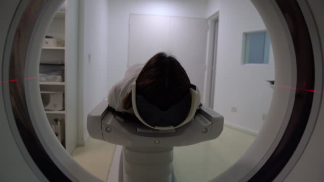 vídeos de stock e filmes b-roll de latin american female patient lying down on cat scan machine ready for the procedure - tumor cerebral