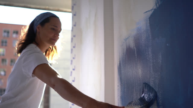Latin American focused woman painting a wall with a blue paint looking very focused