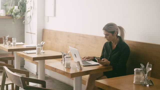 latin american freelancer using smart phone and working with laptop at cafe - owner laptop smartphone video stock e b–roll