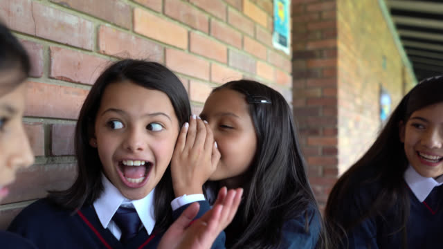 Latin American girls at school telling secrets and looking very happy