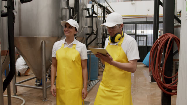 Latin American group of employees working at a brewery factory