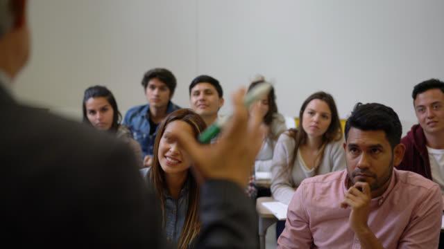 stockvideo's en b-roll-footage met latijns-amerikaanse groep studenten aandacht te besteden aan hun leraar op zoek betrokken sommige glimlachen en sommige gericht - student
