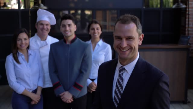 Latin American handsome hotel manager looking at camera smiling and his team standing behind him smiling