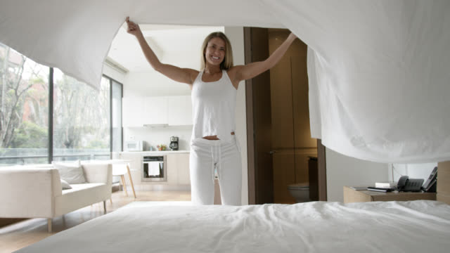 Latin American happy woman making her bed smiling video