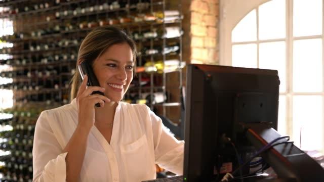 rezervasyon yaparken o sisteme çok neşeyle ekler bir müşteri ile konuşurken latin amerika hostes - sipariş vermek stok videoları ve detay görüntü çekimi