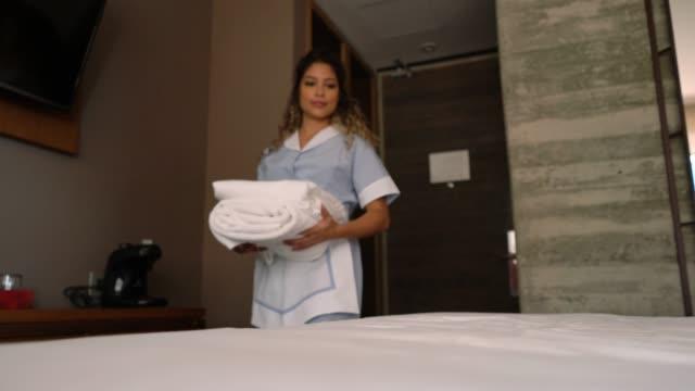 vidéos et rushes de gardien de maison amérique latine mettre des serviettes sur le dessus de lit et de lisser les draps - hotel