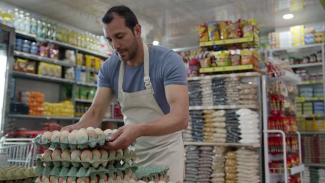 stockvideo's en b-roll-footage met latijns-amerikaanse mannelijke bedrijfseigenaar van een kleine markt die de eivertoning schikt - ei