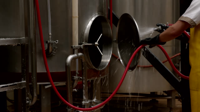 Latin American male employee using a water hose to clean a tank at a brewery video