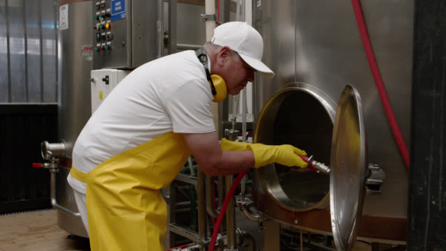 Latin American man cleaning the tanks with water at a brewery factory