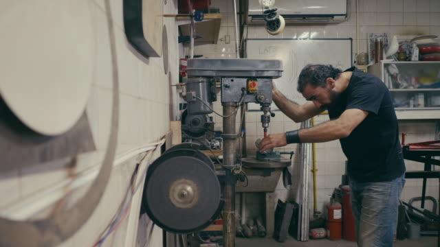 stockvideo's en b-roll-footage met latijns-amerikaanse man boren in de metalen werkplaats - metaalbewerking