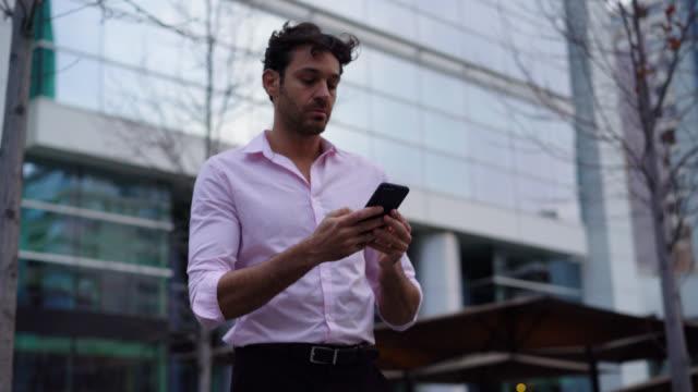 l'uomo latinoamericano in fretta ad aspettare il suo autista guardando lo smartphone e per strada con ansia - aspettare video stock e b–roll
