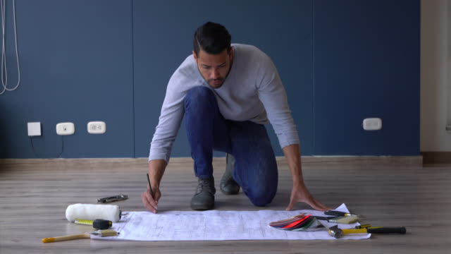 Latin American man making plans while looking at a blueprint of his new home Latin American man making plans while looking at a blueprint of his new home - Lifestyles interior designer stock videos & royalty-free footage