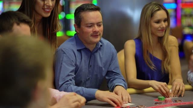 Latin American man playing blackjack at the casino looking happy
