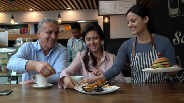Latin American mature couple at a restaurant drinking coffee and friendly waitress bringing their order Latin American mature couple at a restaurant drinking coffee and friendly waitress bringing their order of junk food wait staff stock videos & royalty-free footage