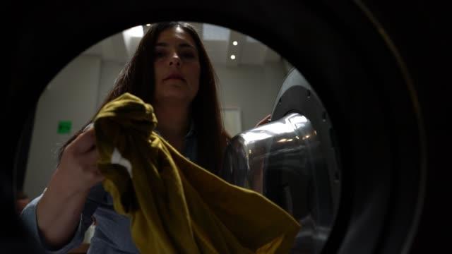 Femelle adulte d'Amérique latine à une laverie libre-service, chargement de la machine à laver - Vidéo