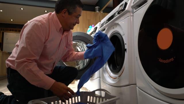 Homme mûr latino-américain, chargement de la machine à laver à une laverie automatique - Vidéo