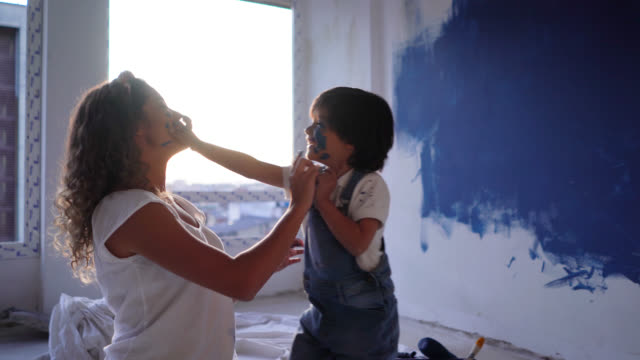 Latin American mother and son making a mess very playfully with paint during a home renovation painting their faces