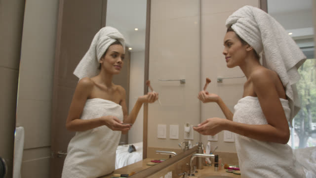 Latin american pretty woman applying make up during her morning routine Latin american pretty woman applying make up during her morning routine - Lifestyles wearing a towel stock videos & royalty-free footage