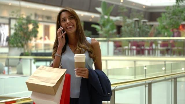 latinamerikansk söt kvinna i gallerian njuter av en kopp kaffe medan du tar emot ett telefonsamtal mycket upphetsad och leende - köpnarkoman bildbanksvideor och videomaterial från bakom kulisserna