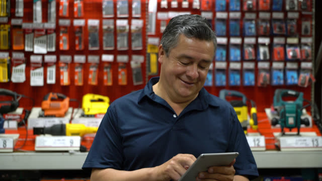 Latin american salesman looking at tablet and then facing camera smiling in a hardware store