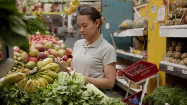 vidéos et rushes de vendeuse latino-américaine faisant l'inventaire des légumes à son étal de marché utilisant un presse-papiers - marché établissement commercial