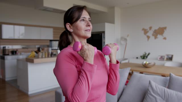lateinamerikanische seniorin zu hause trainieren konzentriert aussehen - entspannungsübung stock-videos und b-roll-filmmaterial