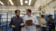 istock Latin american supervisor and blue collar worker discussing while walking through the manufacturing water pump factory 1206325816