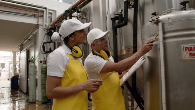 Latin american supervisor training female manual worker at a brewery factory