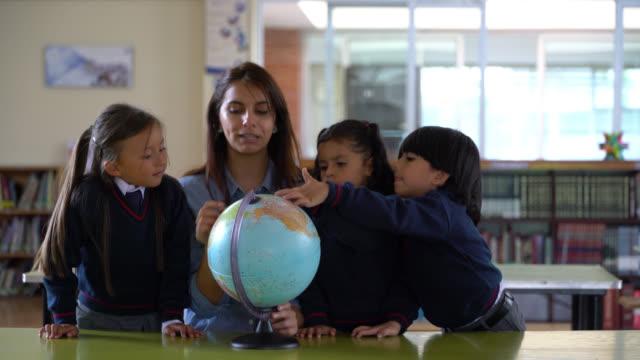 insegnante latinoamericano che spiega qualcosa mentre indica il mondo e gli studenti che prestano attenzione - geografia fisica video stock e b–roll
