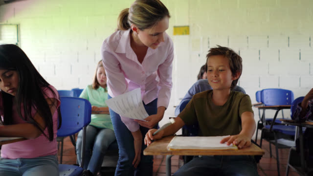 Latin American teacher explaining the homework to confused little boy asking her questions during class Latin American teacher explaining the homework to confused little boy asking her questions during class - Incidental people at background middle school teacher stock videos & royalty-free footage