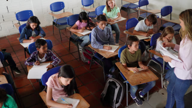 Latin American teacher handing out a homework to each student during class Latin American teacher handing out a homework to each student during class - Education concepts middle school teacher stock videos & royalty-free footage