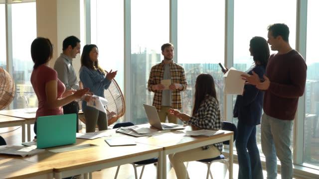 team latinoamericano di millennials durante un incontro applaudendo mentre il leader parla e tiene in mano un tablet - abbigliamento casual video stock e b–roll