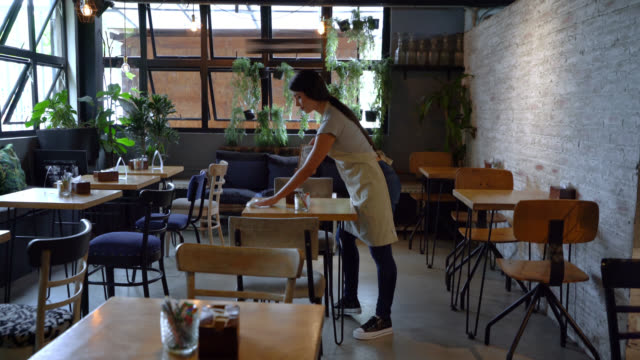 Latin American waitress organizing and cleaning the tables at a restaurant Latin American waitress organizing and cleaning the tables at a restaurant – food service concepts wait staff stock videos & royalty-free footage