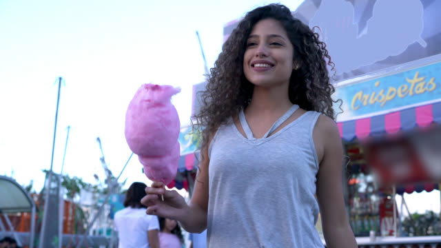 Latin American woman eating a cotton candy while walking around an amusement park looking very happy Latin American woman eating a cotton candy while walking around an amusement park looking very happy and smiling cotton candy stock videos & royalty-free footage