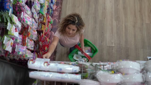 vídeos y material grabado en eventos de stock de mujer latinoamericana agarrando algo de la pantalla de venta al por menor mientras sostiene una cesta con comestibles - snack aisle