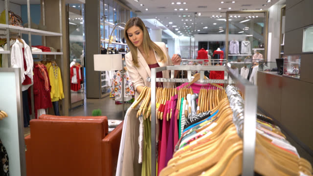 Latin american woman looking at clothes hanging on retail display