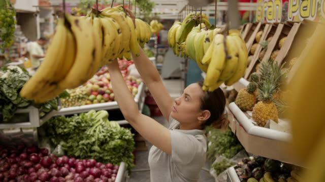 donna latinoamericana che lavora in una bancarella di frutta e verdura che appende banane - mercato frutta donna video stock e b–roll
