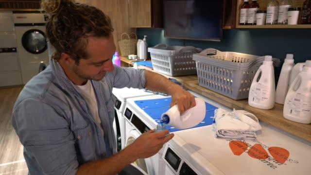 Jeune homme d'Amérique latine à une laverie automatique au cours de détergent dans un sourire mesure de coupe - Vidéo