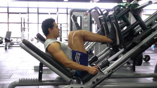 vídeos de stock e filmes b-roll de latin american young man working out his legs on machine at the gym - aparelho de musculação