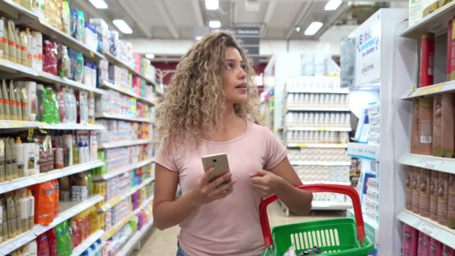 latin american young woman shopping at the supermarket carrying a basket and looking at shopping list on smartphone - igiene video stock e b–roll