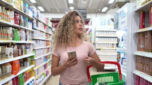 vídeos de stock, filmes e b-roll de compra latino-americana da mulher nova no supermercado que carreg uma cesta e que olha a lista de compra no smartphone - higiene