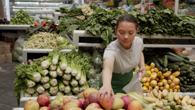 latin american young woman working at a fruit and vegetable market; stall packing mangoes in a plastic bag - mercato frutta donna video stock e b–roll