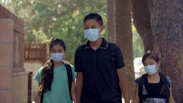 lateinische kinder tragen eine maske zu fuß in richtung schule in los angeles ca usa - stock video - amerikanische kontinente und regionen stock-videos und b-roll-filmmaterial