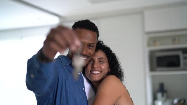 그들의 새로운 집의 열쇠를 들고 라틴어 커플 - home 스톡 비디오 및 b-롤 화면