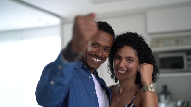 Latin couple holding the keys of their new house